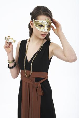 Woman in dress posing in a studio as wearing mask with opera binoculars