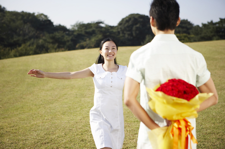 Asian couple posing together in a green field with a bouquet of red roses