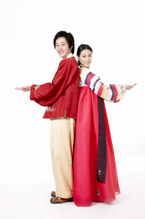 Asian couple wearing traditional korean costume posing in a studio with hand gesture