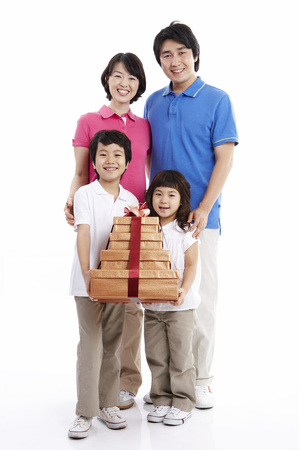 Parents and two children posing together isolated in white with giftboxes