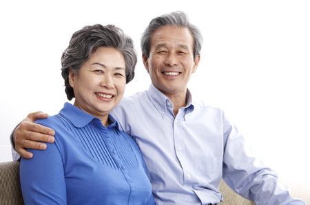 Asian elderly couple posing in a studio sitting on couch