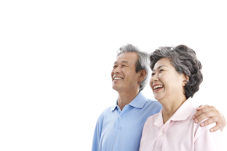 Asian elderly couple posing in a studio as putting arms around on each other