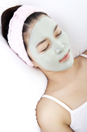 Woman doing applying homemade facial mask isolated in white background 免版税图像 - 85243001