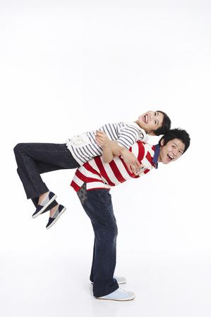 Asian boyfrend carrying girlfriend on back Stock Photo