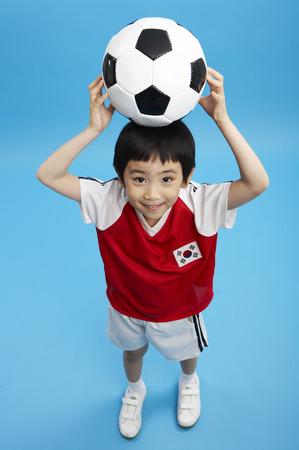 Jonge Aziatische jongen in het nationale team eenvormige stellen met een voetbalbal in een studio