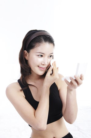 Female Asian putting on makeups isolated in white background studio Stock Photo