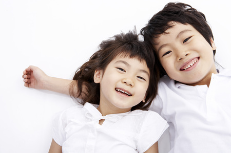 Young Asian boy and girl posing together in a studio as lying on back