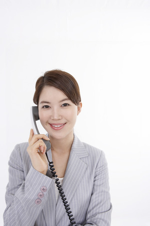 corded: Asian business woman in suit posing in a studio speaking on the landline telephone