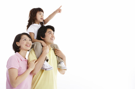 Asian parents and daughter posing in a studio as carrying a daughter
