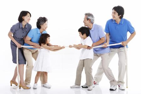 Drie generaties Aziatische familie poseren in een studio als het spelen van een touwtrekken