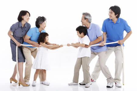 Three generations of Asian family posing in a studio as playing a tug of war Imagens