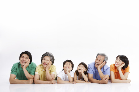 Three generations of Asian family posing in a studio lying on stomach Stockfoto