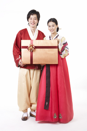 hanbok: Asian couple wearing traditional korean costume posing in a studio with giftbox Stock Photo
