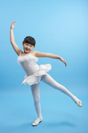 若いアジアの女の子、バレリーナのようなスタジオでポーズをとって白いドレスを着て