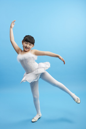 Young Asian girl wearing white dress posing in a studio like a ballerina Reklamní fotografie