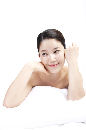 Female Asian with healthy skin posing isolated in clean white background as lying on stomach