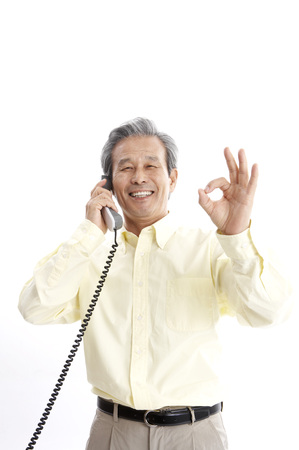 corded: Male Asian elderly posing in a studio with landline telephone