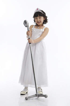 niños actuando: Young Asian girl wearing white dress posing in a studio like a singer Foto de archivo