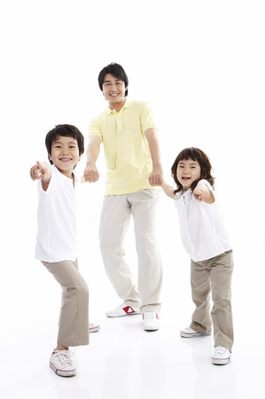 Asian father and two children posing in a studio