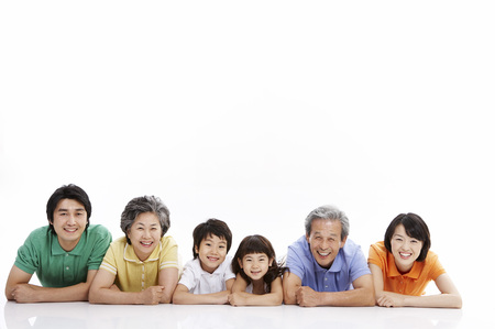 Three generations of Asian family posing in a studio lying on stomach Stock Photo
