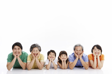 Three generations of Asian family posing in a studio lying on stomach Фото со стока