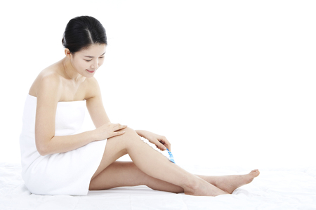 Female Asian wearing towel posing in a white background studio as using razor on legs Stock Photo