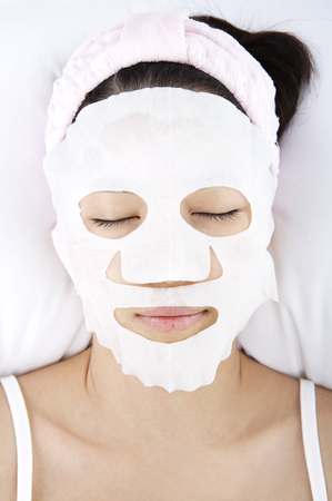 Close up shot of face of woman receiving massages with facial mask 免版税图像 - 85202903