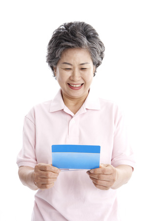 Female Asian elderly posing in a studio with bank passbook