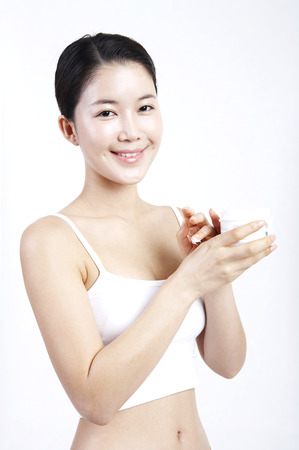 Female Asian doing nail care herself isolated in white background studio