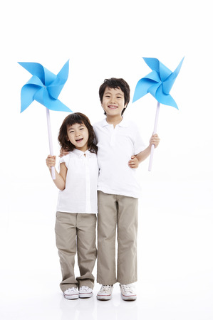 Young Asian boy and girl posing together in a studio with toy pinwheel