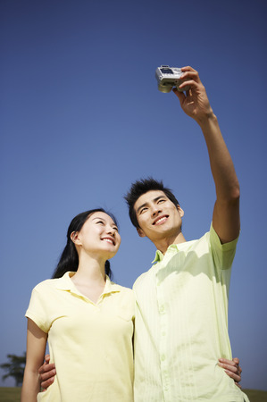 companions: Asian couple posing together in a green field with camera