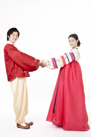 Asian couple wearing traditional korean costume posing in a studio