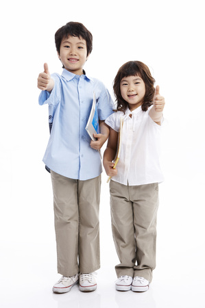 Young Asian boy and girl posing together in a studio with books