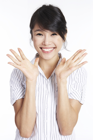 Asian woman posing in a white studio with hand gesture
