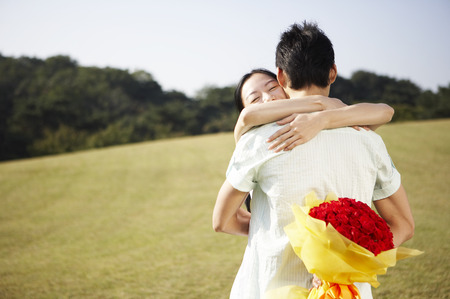Asian couple posing together in a green field with a bouquet of red roses Stock Photo