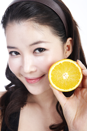 Close up shot of Woman with healthy skin posing in a studio with orange