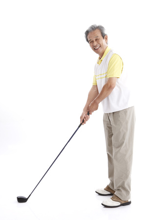 Male Asian elderly posing in a studio with golf clubs Stock Photo