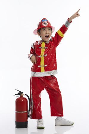 화재 소화기와 스튜디오에서 포즈를 취하는 소방 관 유니폼을 입고 젊은 아시아 소년 스톡 콘텐츠