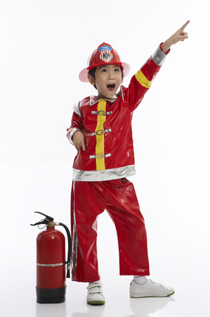 Young Asian boy wearing firefighter uniform posing in a studio with fire extinguisher