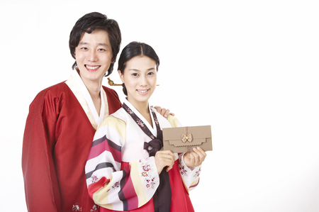 Asian couple wearing traditional korean costume posing in a studio with gift money envelope Stock Photo