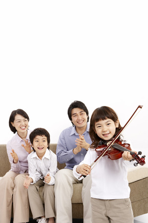 Parents and two children posing together isolated in white as listening to daughter palying the violin