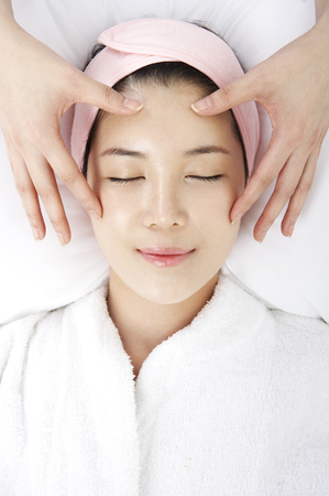 Close up shot of face of woman receiving massages with masseuse hands Stock Photo