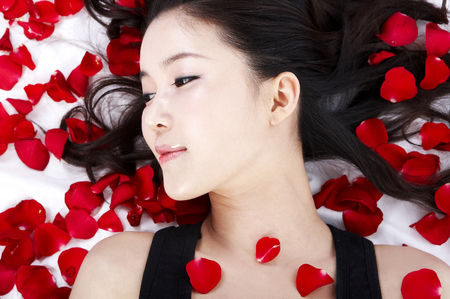 Close up shot of female Asian posing as lying down on red rose petals