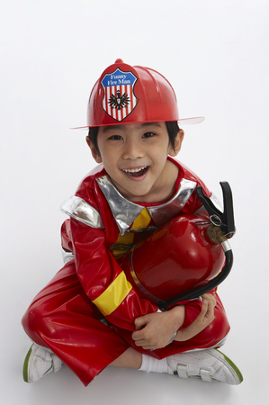 niños actuando: Young Asian boy wearing firefighter uniform posing in a studio with fire extinguisher