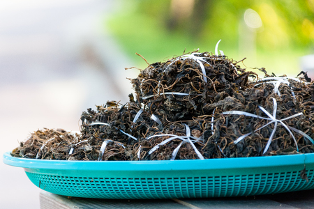 Stacked dry wild greens on a plastic basket Stock Photo