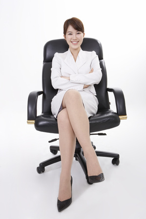 Asian business woman in suit posing in a studio sitting in a chair with legs crossed