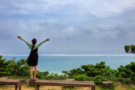 Back shot of a woman opening arms upward looking out the ocean Stock Photo
