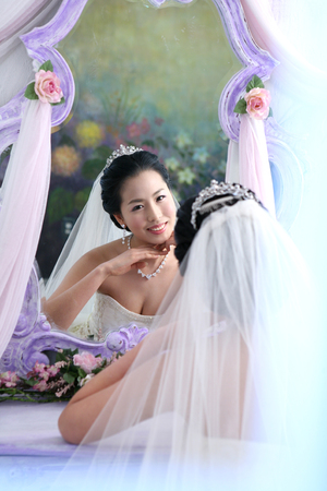 mirror image: Asian bride in wedding dresses posing in a studio with reflection on mirror