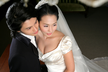 Close up shot of Asian bride and groom in wedding dresses posing in a studio