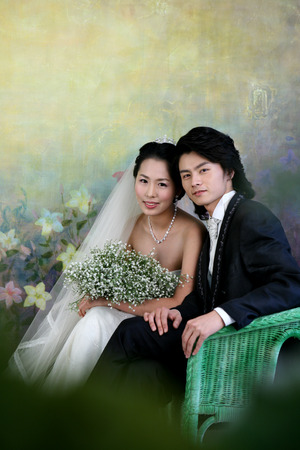 Asian bride and groom in wedding dresses posing in a studio as sitting down with a bouquet of flowers